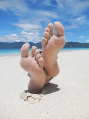 Sandy feet on a tropical beach