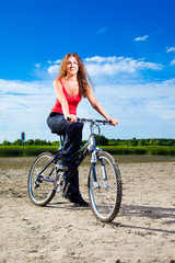 beautiful woman with bicycle at the sea