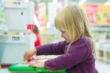 Adorable girl draw on plastic tablet in shop