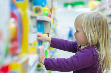 Adorable baby with toys on shelves in mall