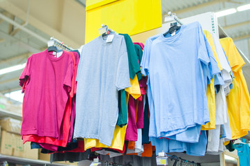 Variety of color t-shirts on stand in supermarket
