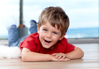 three years old boy on the floor, having fun
