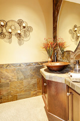 Metal Sink with wood cabinet and stone tiles.