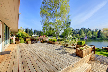 Large wood deck with lake and spring landscape.