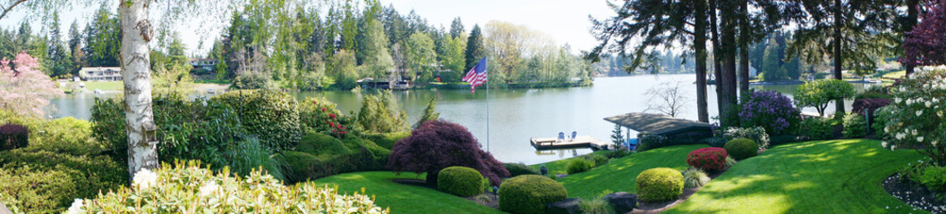 Back yard landscape with spring blooming flowers and lake.