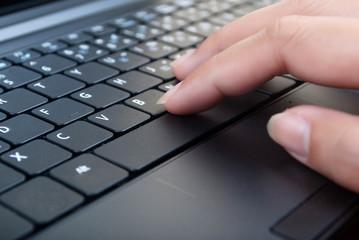 Hand pushing laptop keyboard.