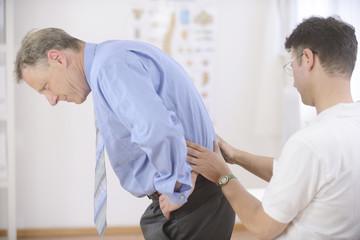 Physiotherapy: Physiotherapist examining senior man