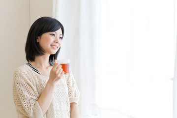 a young asian woman drinking tea