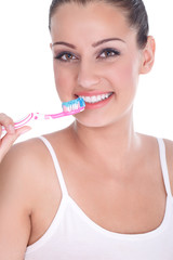 Beautiful young woman brushing her teeth