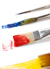 Paintbrushes with ink are lying on white background, isolated