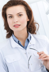 Portrait of dentist's assistant with glasses, white background