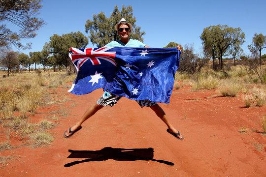 Jeune homme sautant avec le drapeau australien