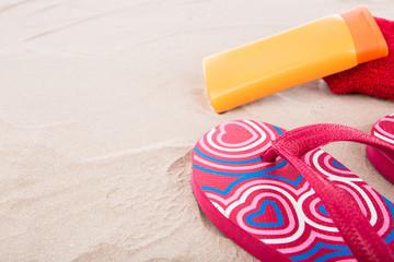 Flipflops ,sunscreen,towel on sand beach