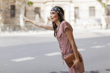 beautiful model with a headscarf calling a cab