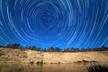 stars around the Pole Star in the background of the river