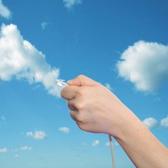 Conceptual human hand holding a internet data cable in clouds