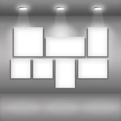 Empty frames on dark wall in gallery interior