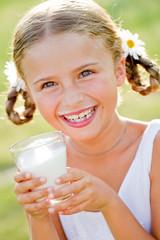 Portrait of lovely girl drinking fresh milk outdoors