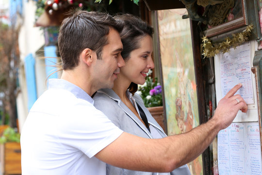 Couple in Paris looking at restaurant menu