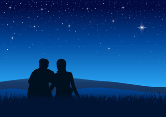 Couples sitting on the grass watching the night sky