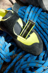 Vertical shot of rock climbing boots and safety rope