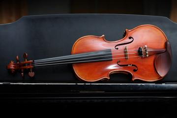 violin on black piano.