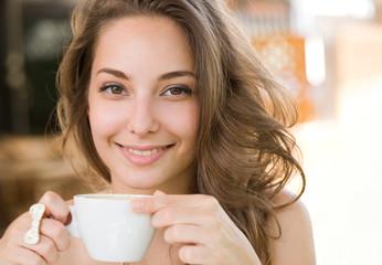 Beautiful young brunette enjoying coffee.