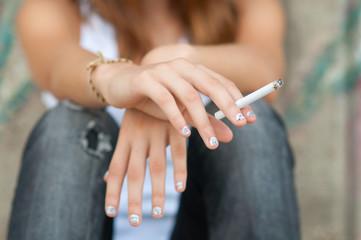 Teenage hands holding cigarette
