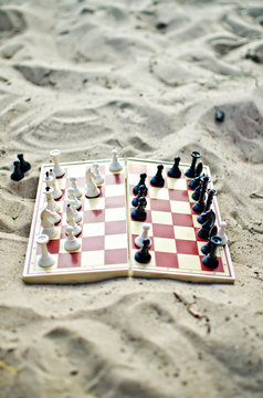 Chessboard with figures on it on the sand
