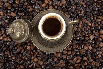 Cup of black coffee on a saucer on roasted coffee beans