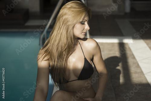 Sexy indian woman by dark pool in black bikini