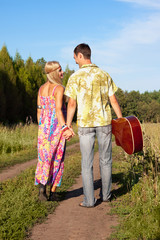 young woman and man with guitar go on road