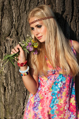 beautiful blonde with flowers stand by tree