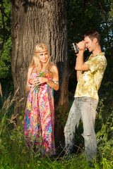 fine blonde with flowers stands by tree.and young man holding fi