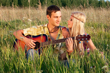 cute young man and fine woman sit on meadow. young man plays  gu
