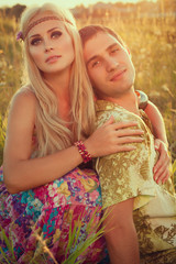 cute young man and fine woman sit on meadow against sunset.