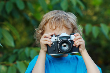 Little cute blond boy with a camera shoots you outdoors