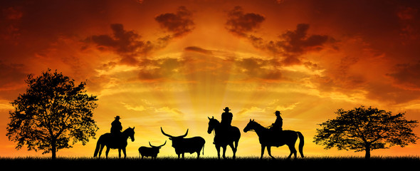 Silhouette cowboys with horses in the sunse