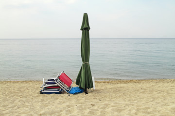 End of summer. Closed parasol and chairs on an empty beach