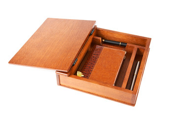 Wooden casket with  notebook and pens on a white