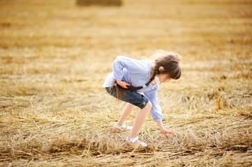 Little girl picking up straws on field