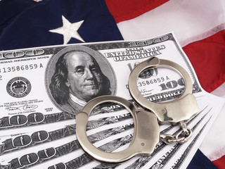 100 Dollar Bills And Hand Cuffs Over American Flag