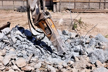 Escavatore con martellone demolisce struttura in cemento armato