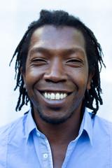 Close up portrait of a black Jamaican man with dreadlocks.