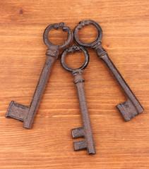 Three antique keys on wooden background