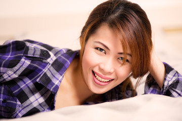 Woman in purple plaid shirt lying in bed