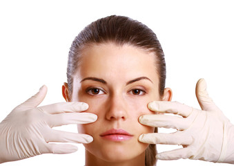 Hands of a surgeon touching the face