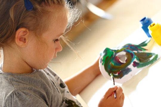 Little girl painting a carnival mask