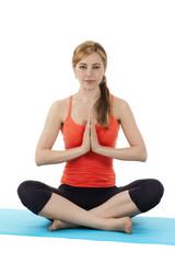 junge frau beim yoga auf einer matte vor weißem hintergrund