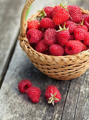 Obraz fresh raspberry in a basket on wooden table - fototapety do salonu
